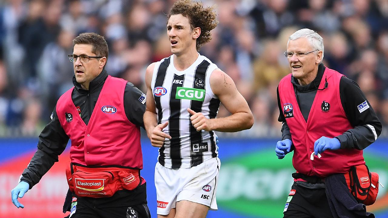 Chris Mayne is helped from the ground by trainers during Saturday's win over Geelong. Picture: Quinn Rooney/Getty Images.