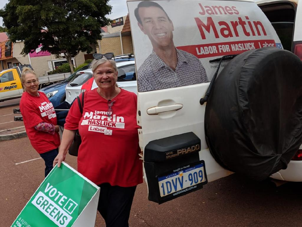 A Labor supporter with a Greens placard.