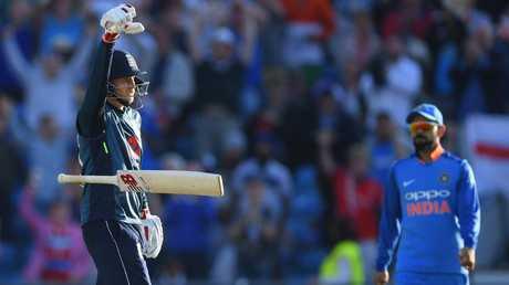 Joe Root celebrates his century off the last ball of a match against India. Virat Kohli looks unimpressed.