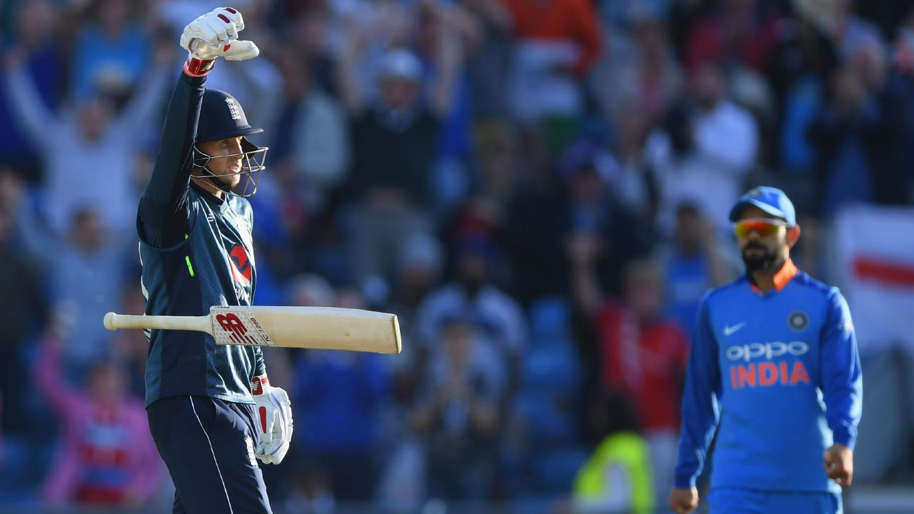 Joe Root celebrates his century off the last ball of a match against India. Virat Kohli looks unimpressed.