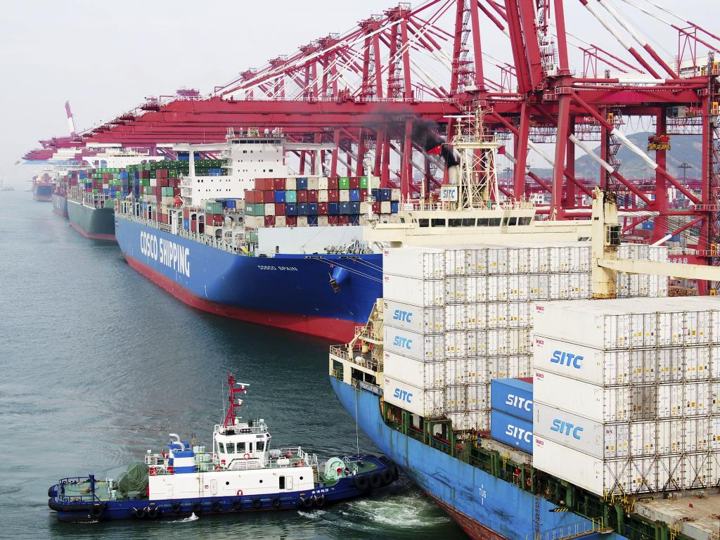 A barge pushes a container ship to the dockyard in Qingdao in eastern China's Shandong province. President Donald Trump's latest tariff hikes on Chinese goods took effect Friday and Beijing said it would retaliate. Picture: AP