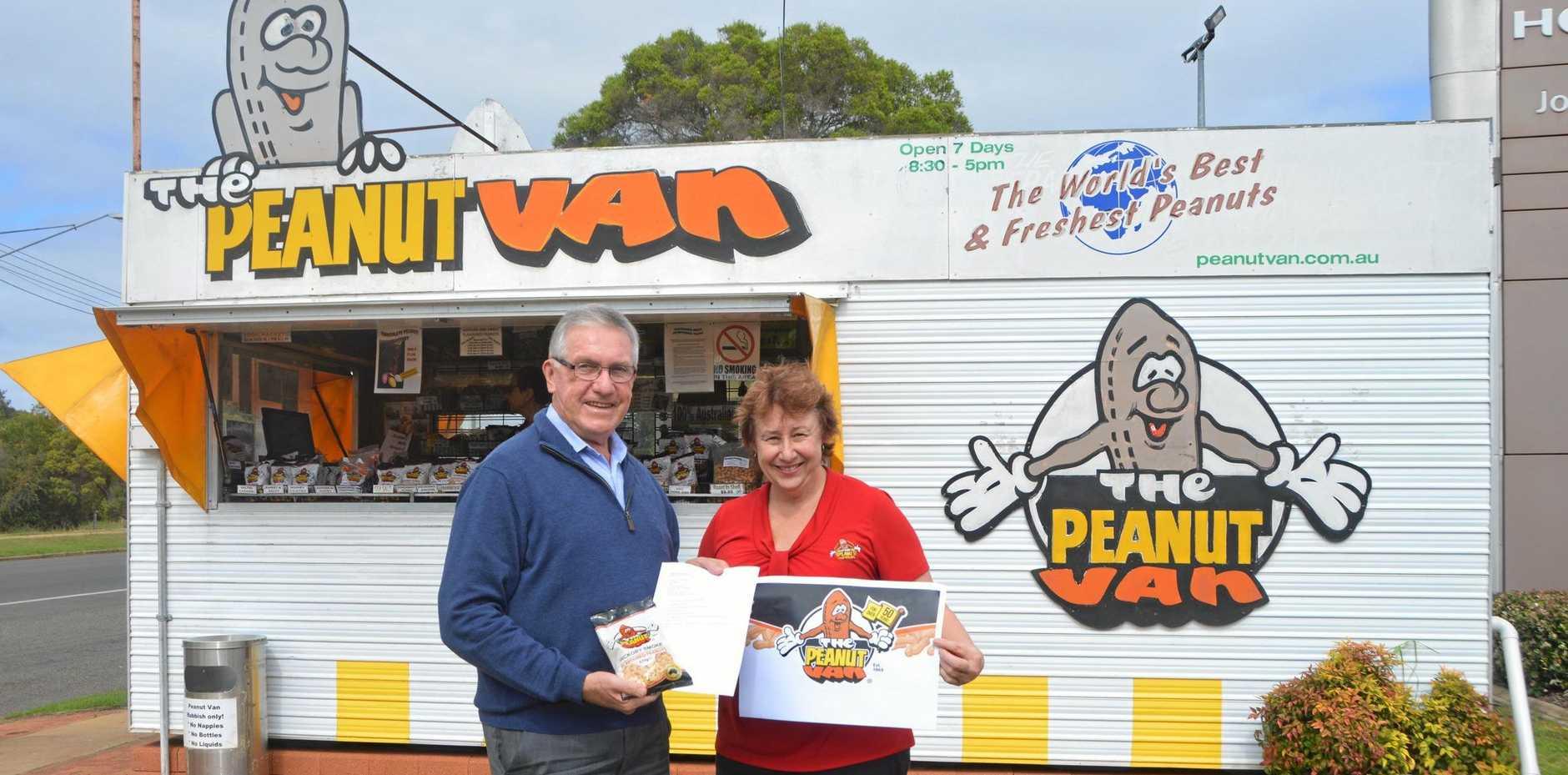 South Burnett Mayor Keith Campbell hands Peanut Van manager Rowena Dionysius his top secret recipe for the cookbook.