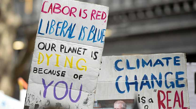 Protesters hold placards during a rally on climate inaction outside the Liberal Party headquarters in Melbourne, Friday, May 3, 2019.