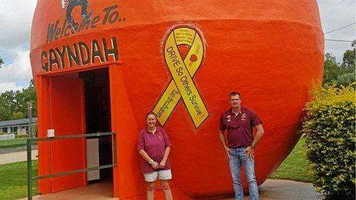 ORANGE GOES YELLOW: Tania Richards with Transport and Main Roads' Wayne Crofts next to the Big Orange's new ribbon.
