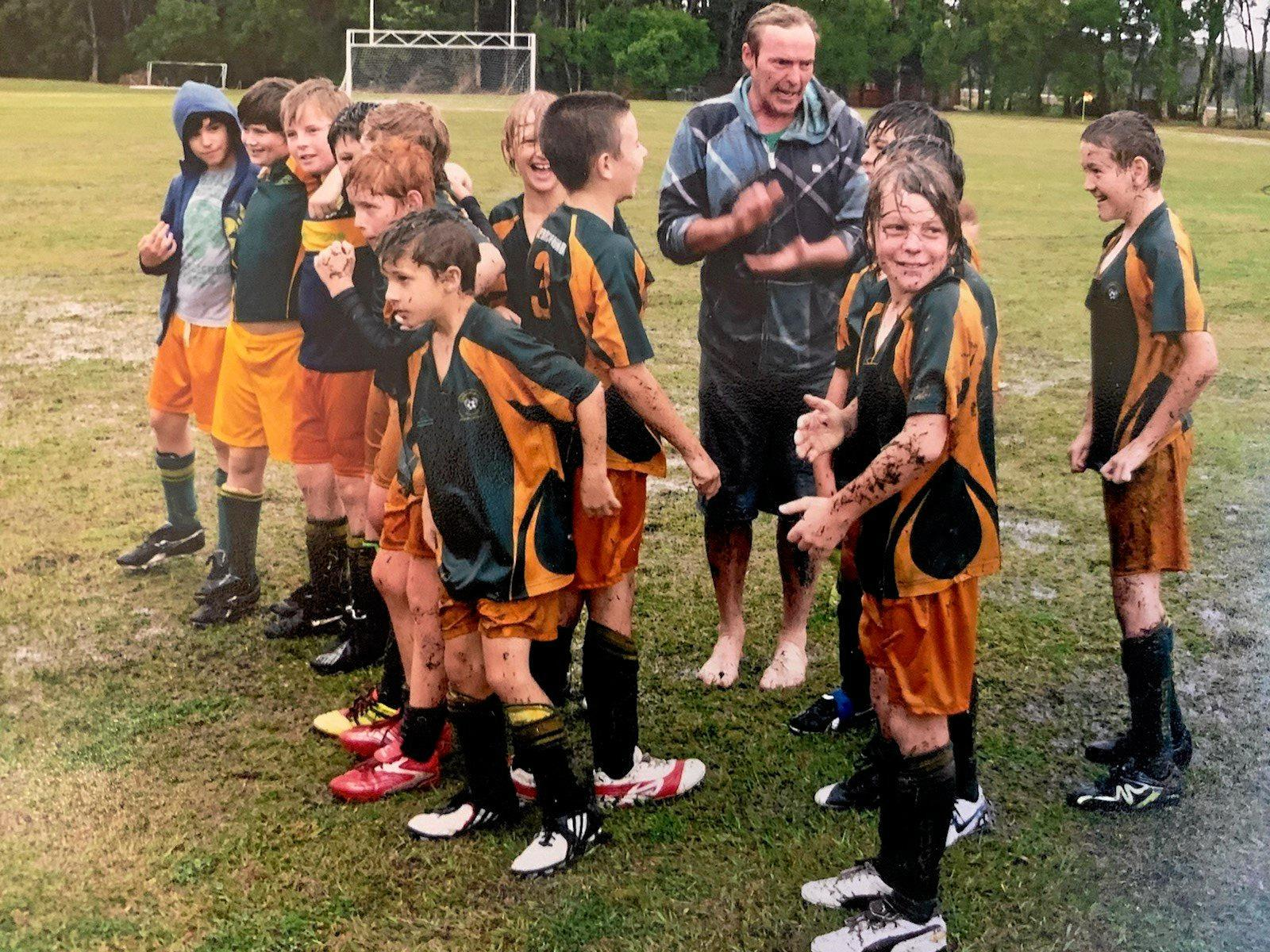 HAPPINESS IN MUD: Bodhi Aufmanis (second from right) and his teammates after his dad Steve Aufmanis promised them a mudslide if they won the preliminary finals when he was 11.