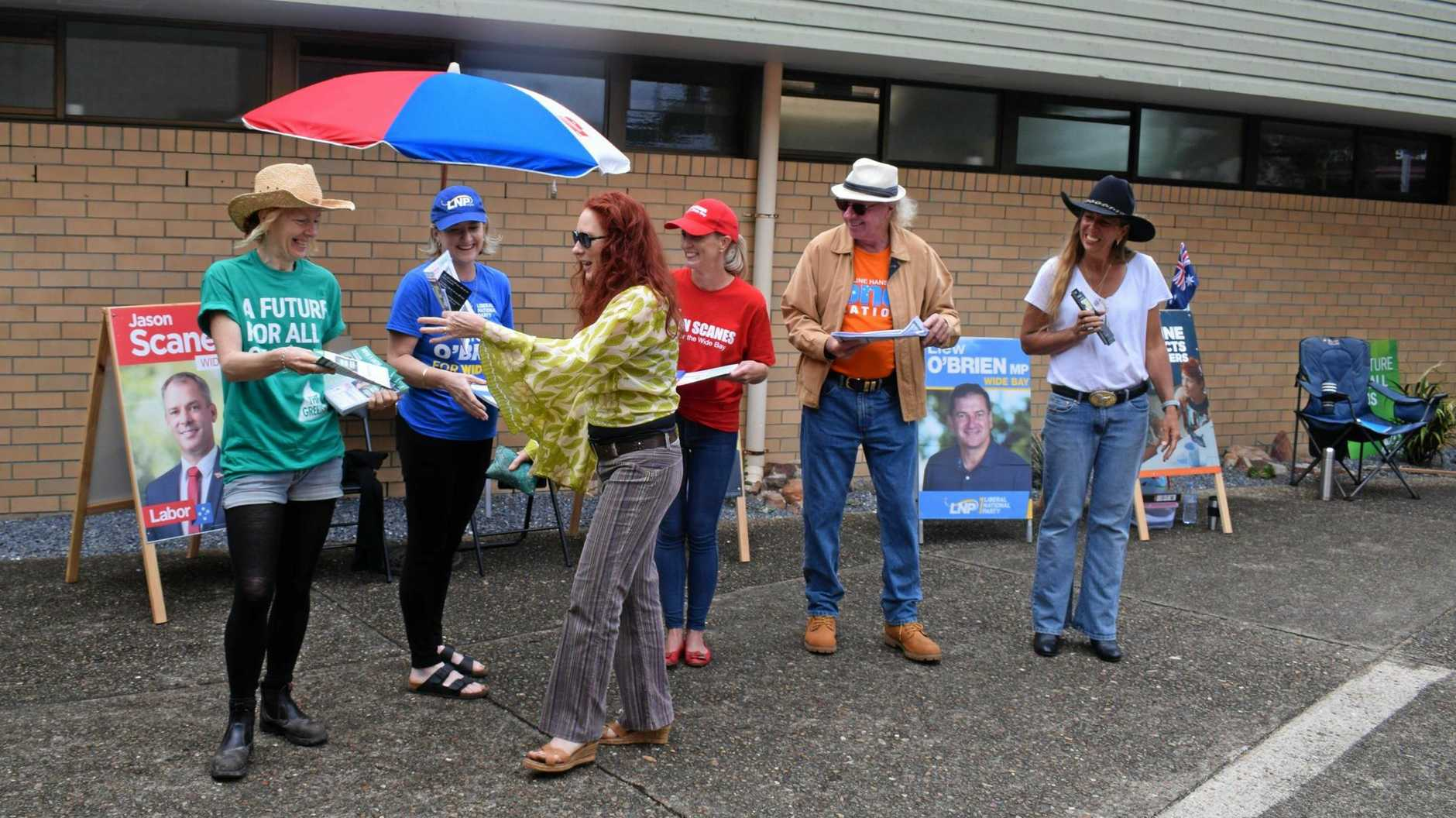 A voter runs the gauntlet of party promoters at Gympie's Senior Citizens Centre.
