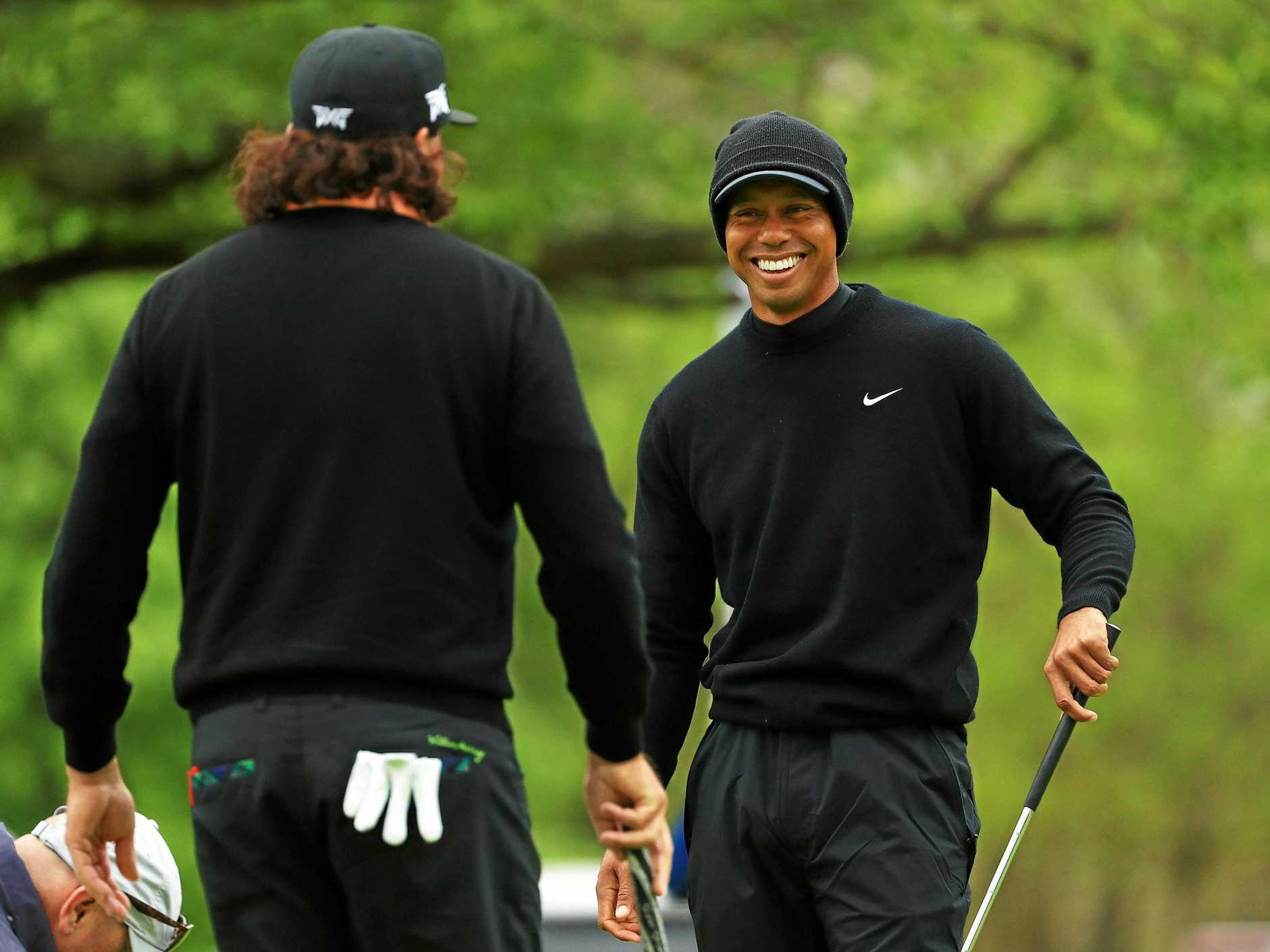 Tiger Woods shares a moment with Pat Perez on the practice green at the Bethpage Black course. Picture: Mike Ehrmann/Getty Images