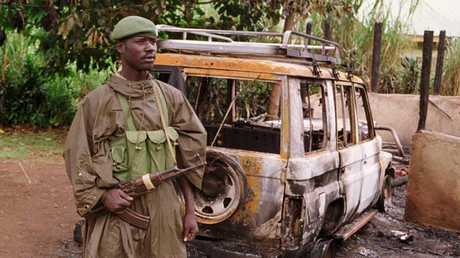 A Ugandan soldier standing by wreckage of burnt out vehicle destroyed during the tourist massacre in 1999. Picture: Supplied