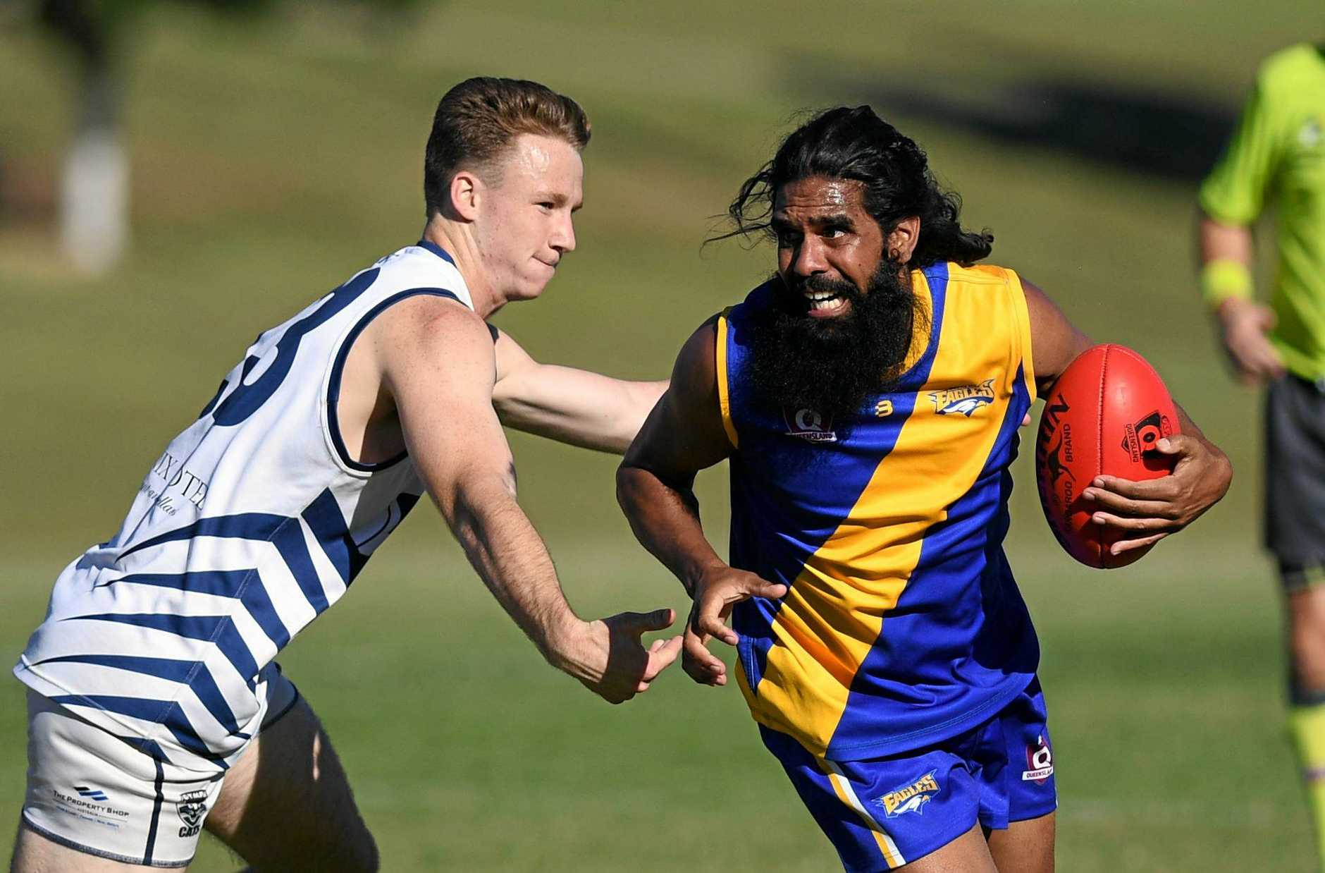 Ipswich Eagles player Kapun Morris looks to fend off a Gympie chaser in last weekend's win at Limestone Park.