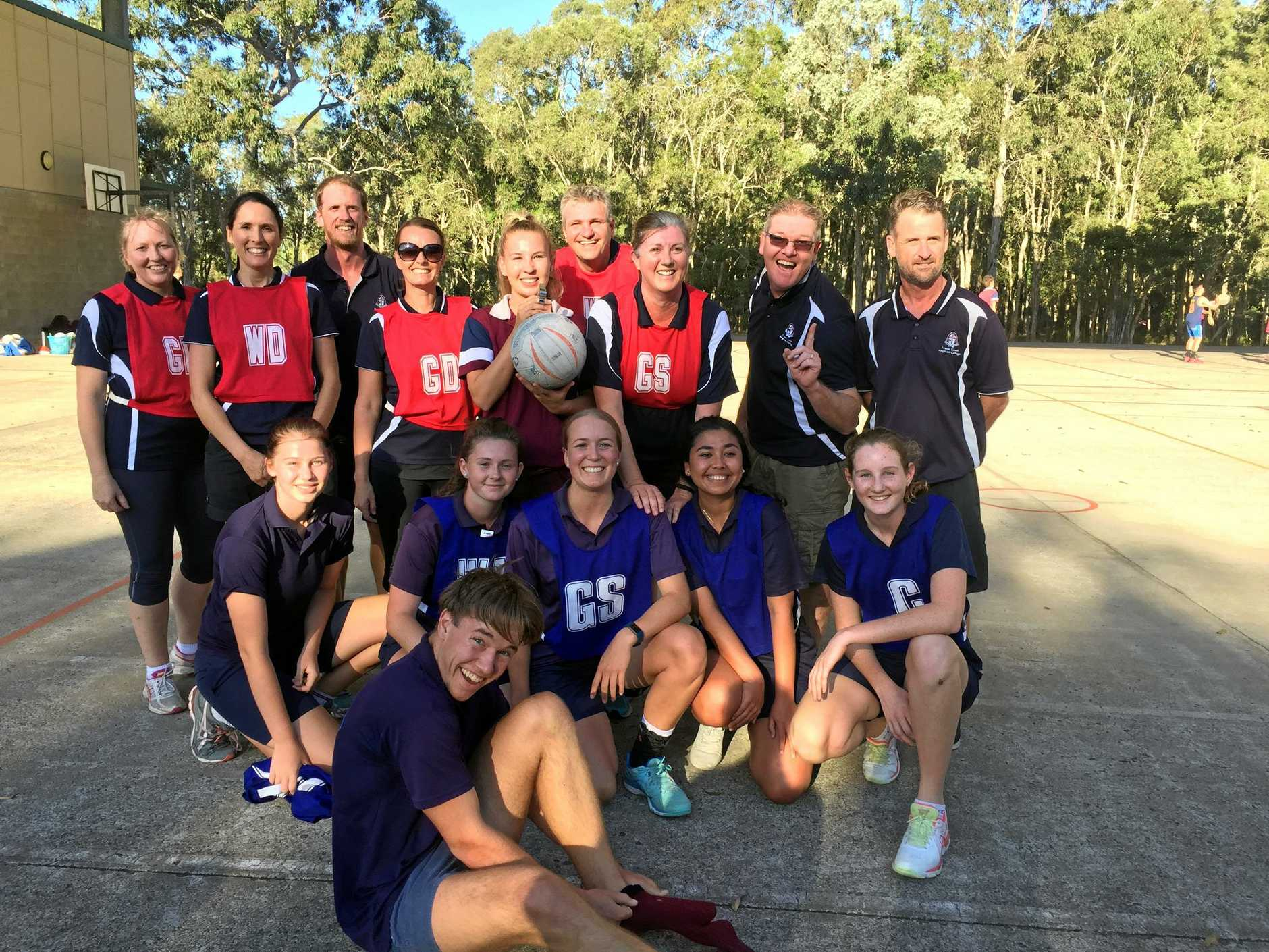 VOLUNTEER: Lesley Smith, inset and wearing sunglasses in the GD red bib, as part of the Staff v Students netball game held at the Fraser Coast Anglican College in 2018.