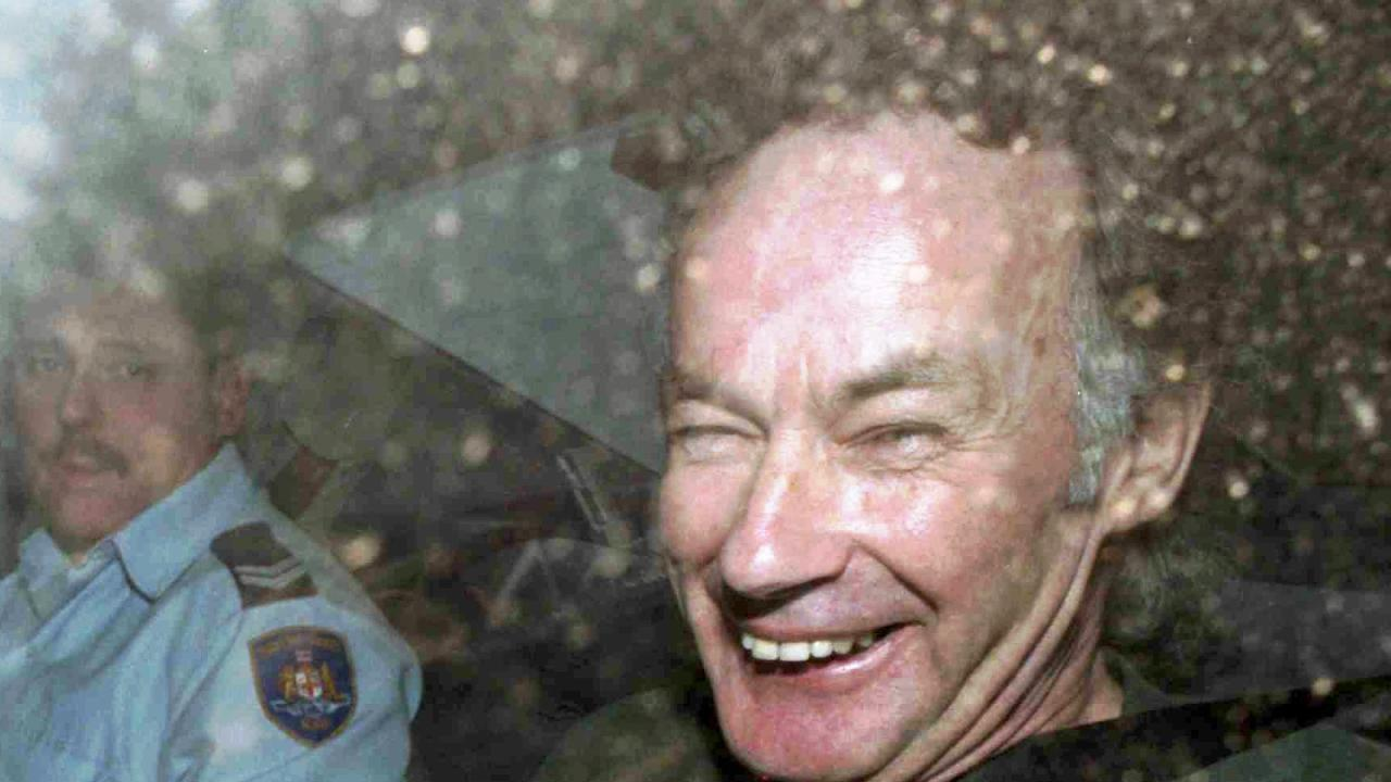 Convicted serial killer Ivan Milat smiles in a police car after attending a court in 1997.