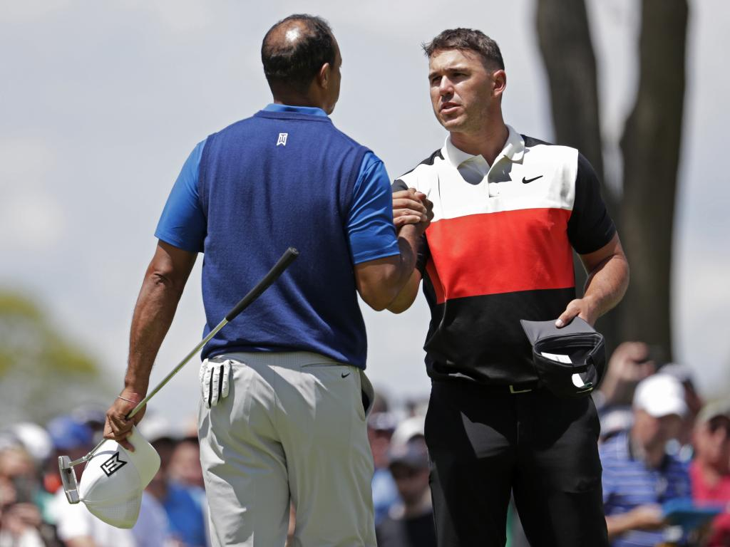 Brooks Koepka shakes hands with Tiger Woods after finishing the first round. (AP Photo/Julio Cortez)
