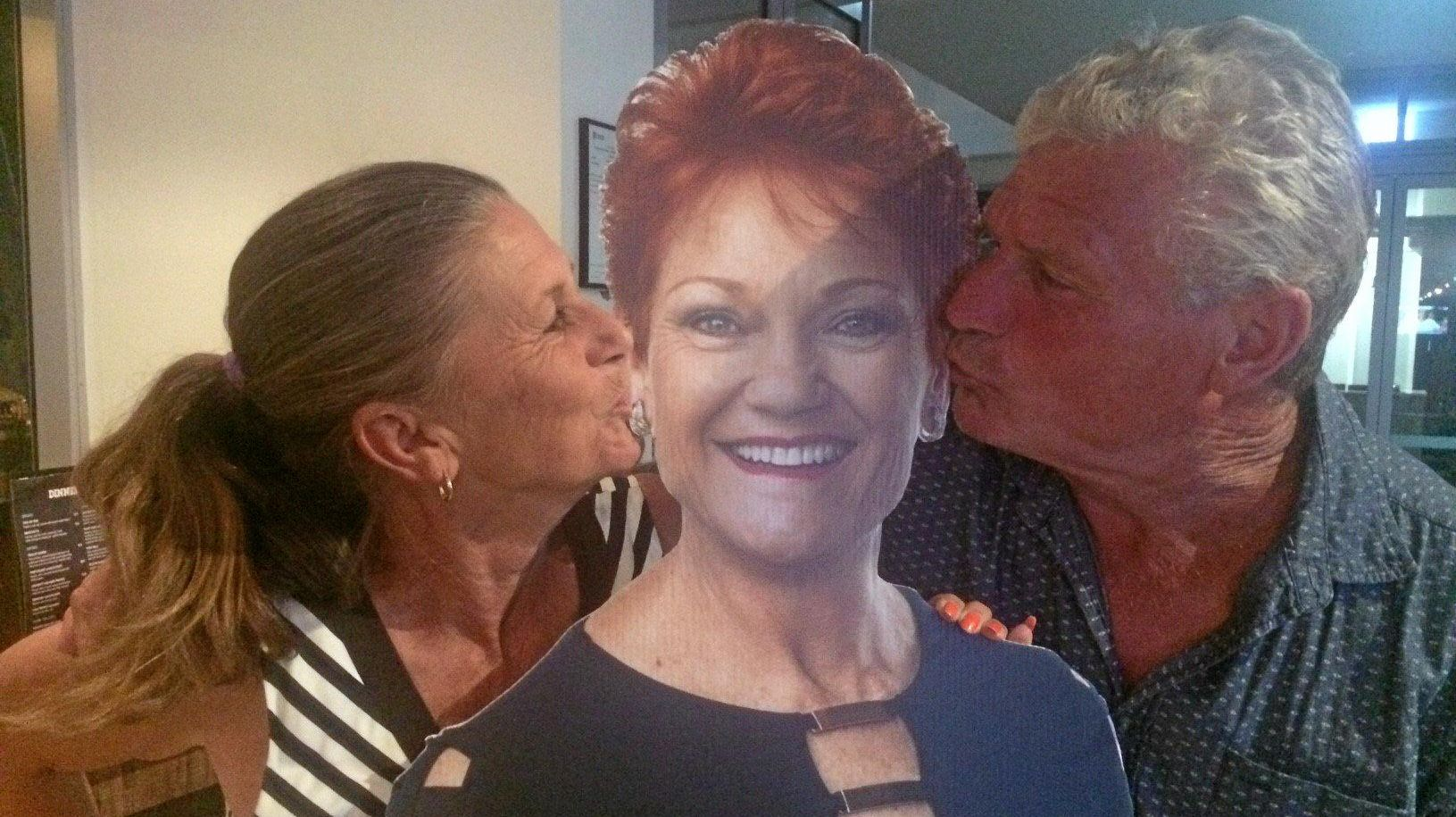One Nation candidate Deb Lawson and her husband Peter Andrews kissing a cardboard cut-out of Pauline Hanson.