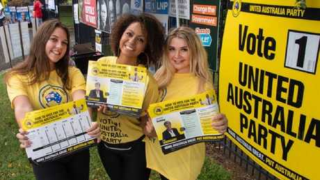 Backpackers Mira Sutton (UK), Ali Cofta (Brazil), and Katie May (UK) handing out Clive Palmer's United Australia Party how to vote cards at the Parramatta State School in Cairns. Picture: Brian Cassey