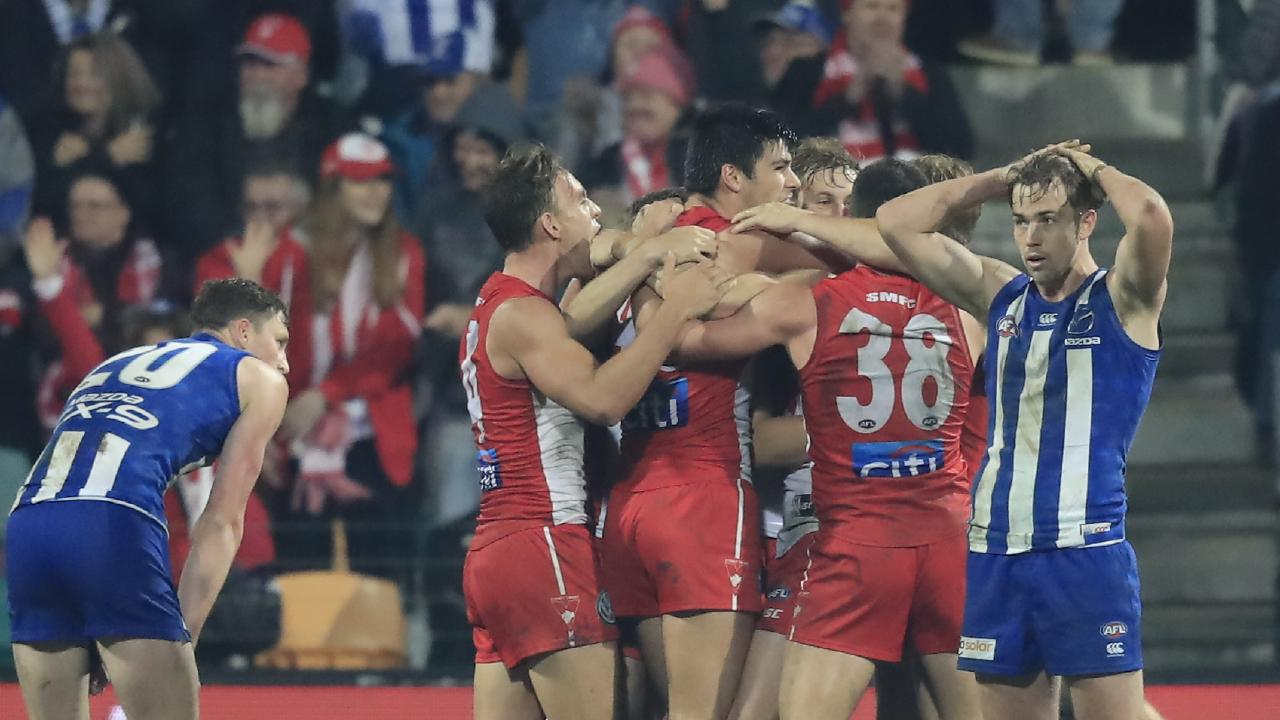 Sydney's defenders celebrate on the final siren after holding off North Melbourne's late rally in Tasmania. Picture: AAP Image/Rob Blakers.