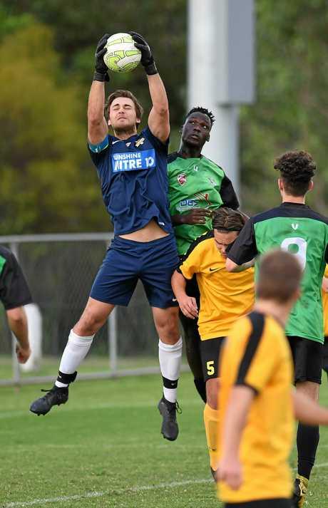 Ipswich Knights under-20 footballer Lucky Joe flies high with the Sunshine Coast goalkeeper in their Saturday afternoon clash at Bundamba. The Knights won 3-1.