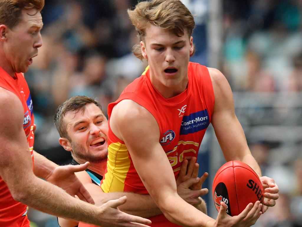 Charlie Ballard of the Suns is tackled by Sam Gray of the Power.