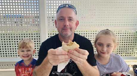 Richard Roberts with son Riley Roberts, 5, and daughter Abby Roberts, 8, enjoying the sausage sizzle