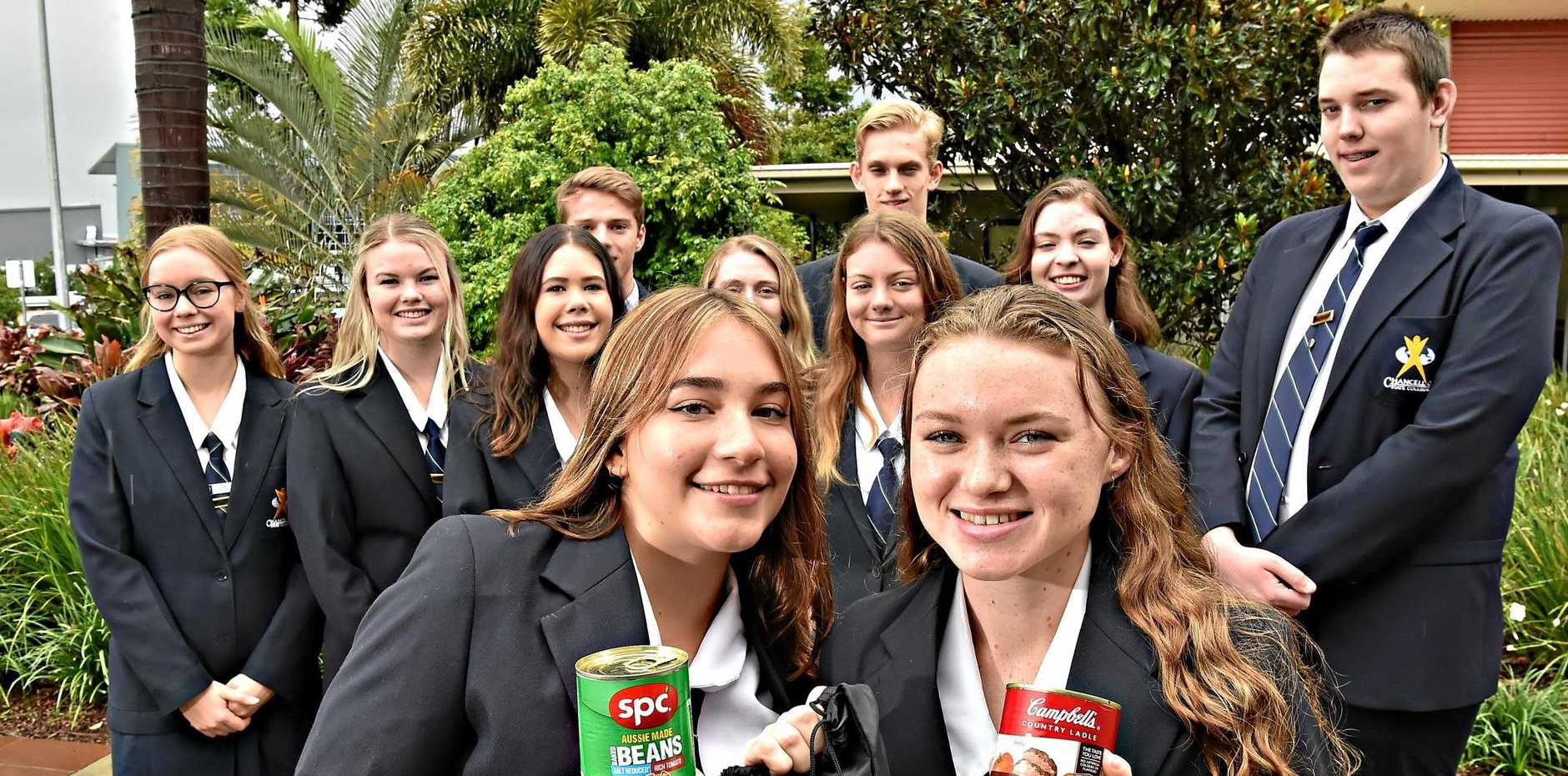 Year 12 Chancellor State College collecting cans of food for homeless people. Kenya Nebauer and Aviendah Dwyer-Flynn (front) with cans of food.