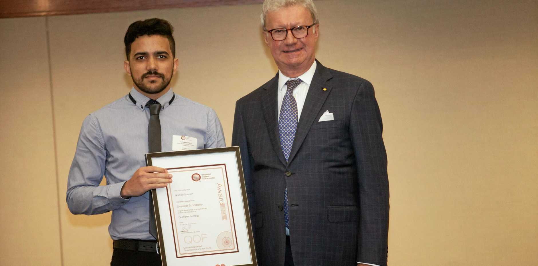 Gladstone electrician Nathan Dunnett receives a Queensland Overseas Foundation award from Governor of Queensland,  Paul de Jersey at Parliament house on March 15.