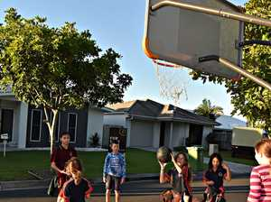 Children play under a basketball hoop in Frogmouth