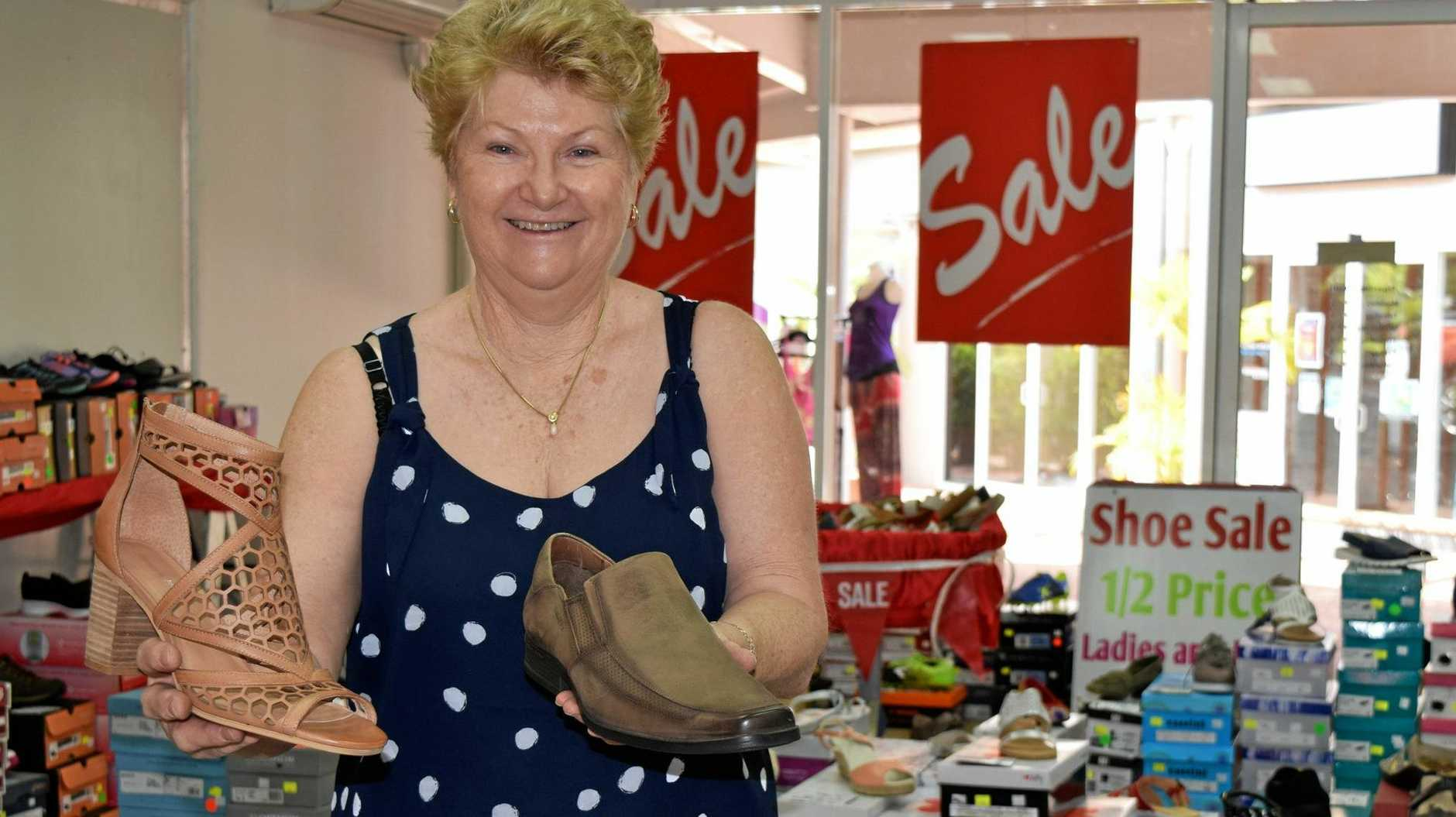 GRAB A BARGAIN: Pam Allison shows off some of the shoes on offer at the pop-up clearance shop in Cannonvale.