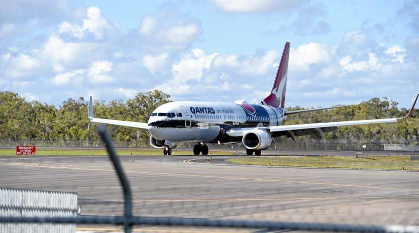 A Qantas plane landing at an airport.