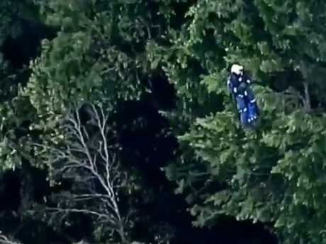 A rescuer gets winched at the scene. Picture: Channel 9