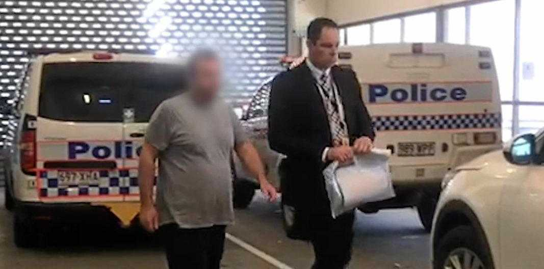 A 39-year-old man is escorted to Tweed Heads Police Station after he was extradited to New South Wales from Brisbane Magistrates Court on Tuesday.