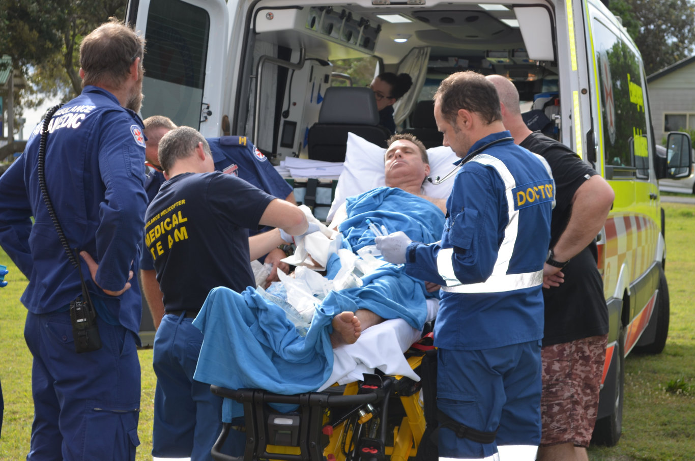 One of the men a marlin has speared when it got into their boat off Wooli on Thursday, receiving treatment before he was flown to Coffs Harbour hospital.