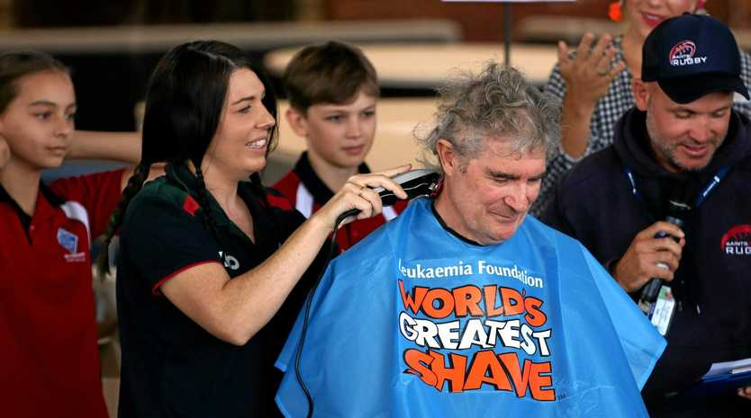 Student Felicity Greenback shaves her father Mal's head.
