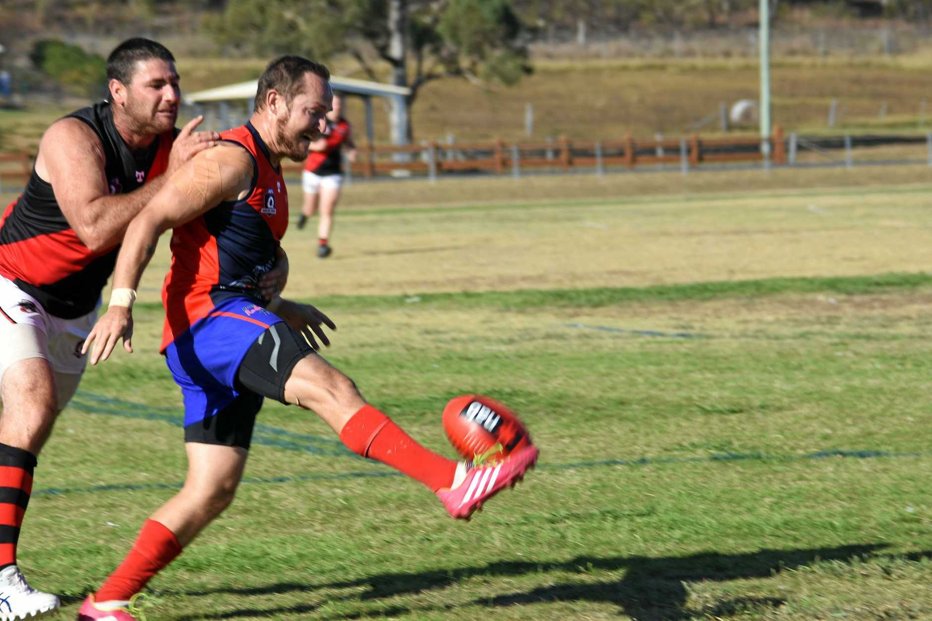 Warwick Redbacks AFC player Tyhe Clarkson (right) punts the ball in the team's match against the South Toowoomba Bombers.