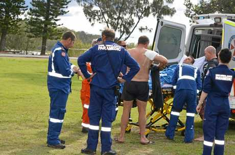 One of the men injured when a marlin got into their boat, with the bandaged arm, watches as his more seriously injured mate is loaded into the Westpac Rescue Helicopter for the flight to Coffs Harbour Hospital.