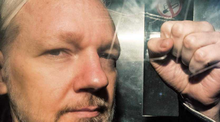 WikiLeaks founder Julian Assange gestures from the window of a prison van. Picture: AFP