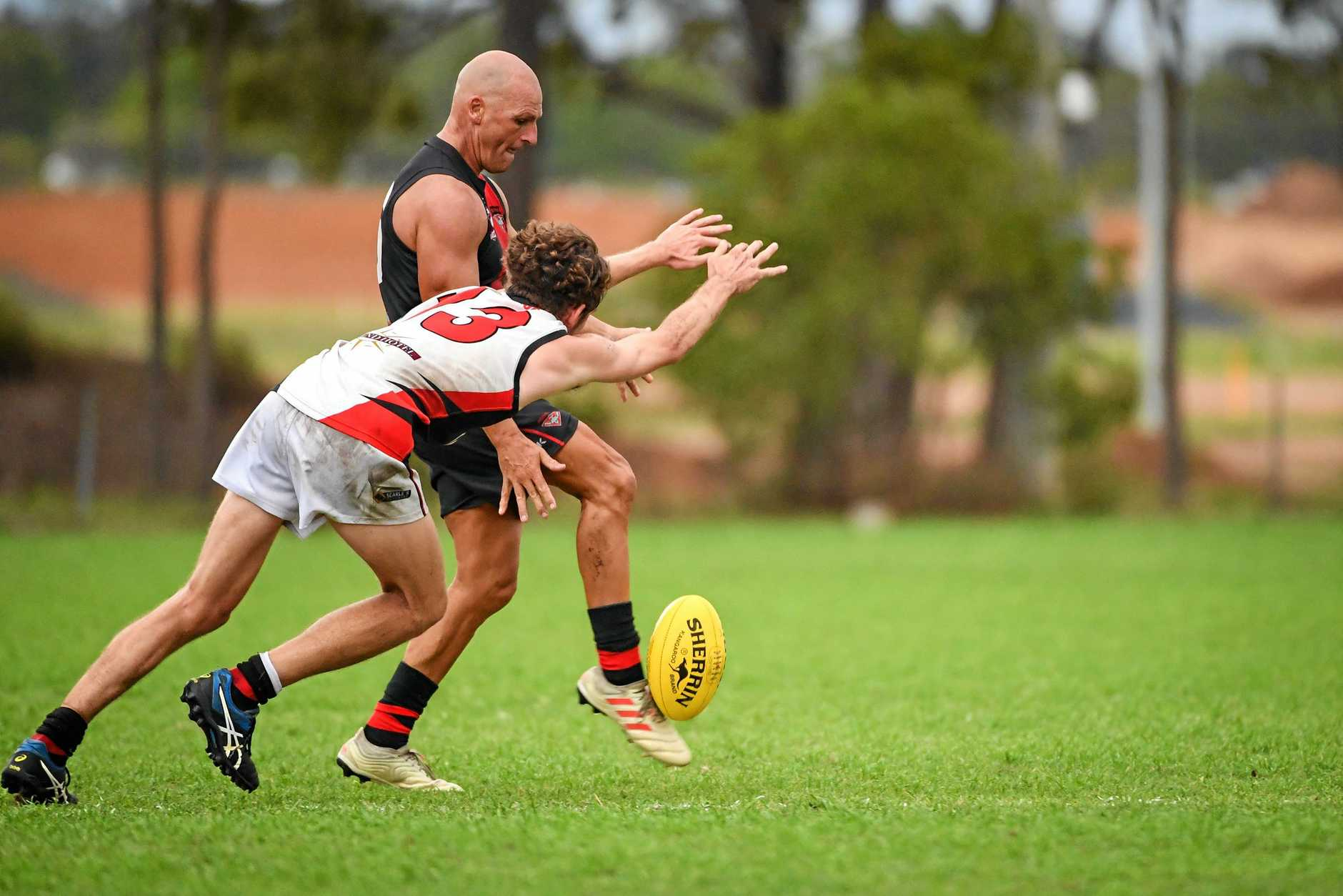 UNDER PRESSURE: Brothers Bulldog Bryce Lewis attempts to smother a kick by Hervey Bay Bombers player Dean Stanley.