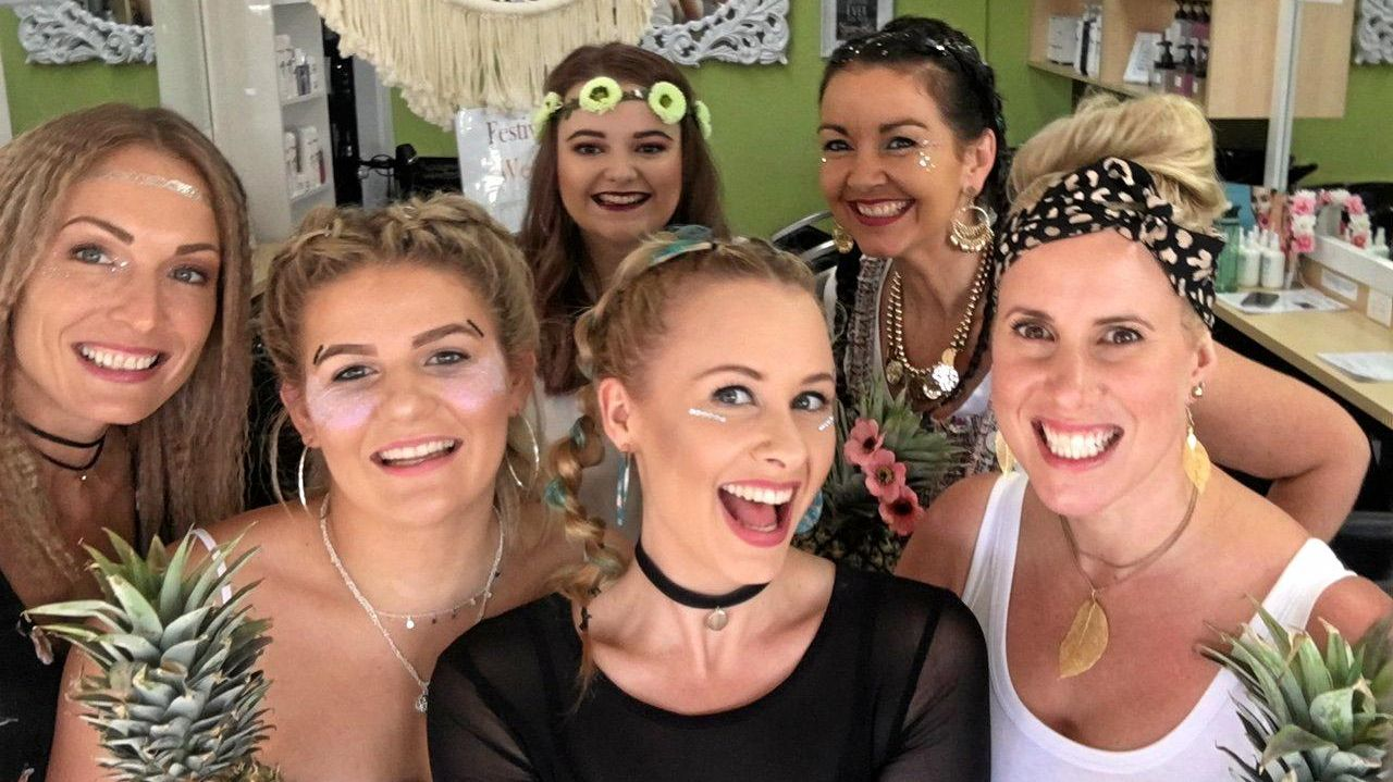 The Uptown Hair Studio team in Nambour has enjoyed a week-long festival in the lead up to today's Big Pineapple Music Festival, with pineapple-replica hairstyles, glitter and fresh produce. Owner Rhonda Billett (back right) said the town and surrounds had enjoyed the good vibes and economic boost.
