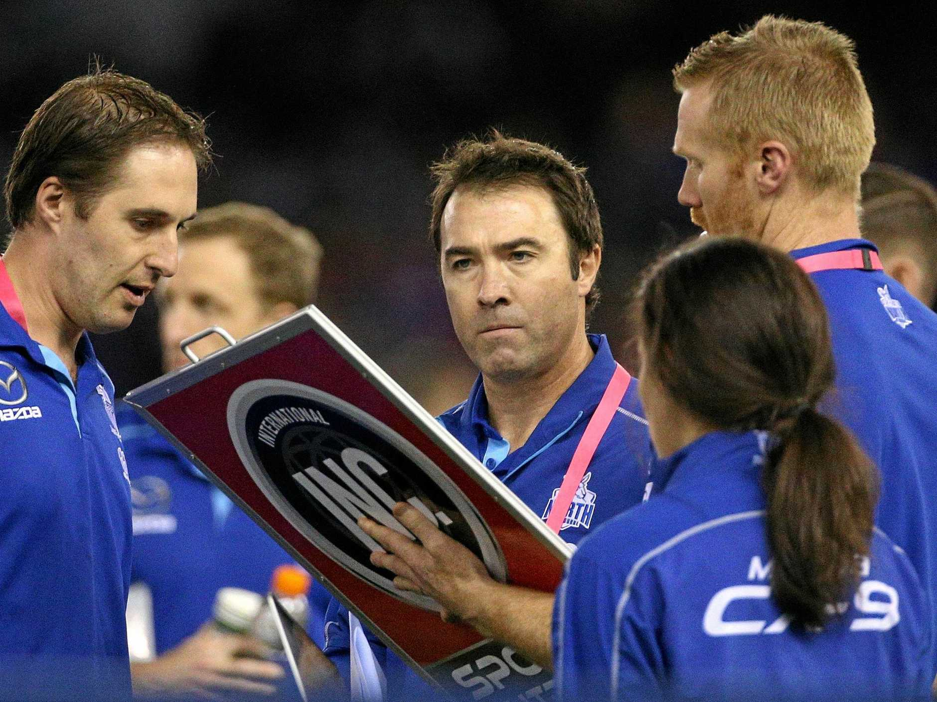 Kangaroos coach Brad Scott, centre, liaises with his staff during his side's clash with the Western Bulldogs at Melbourne's Marvel Stadium on Saturday afternoon. Picture: Hamish Blair/AAP