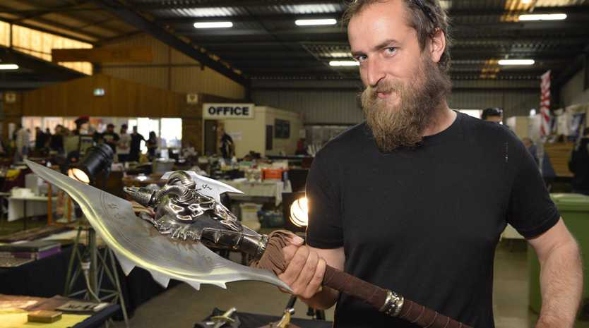 Myles Cockburn gets the feel of a World Of Warcraft Shadowmourne axe at the Gun, Militaria and Collectables Show at Toowoomba Showgrounds, Saturday, May 25, 2019.
