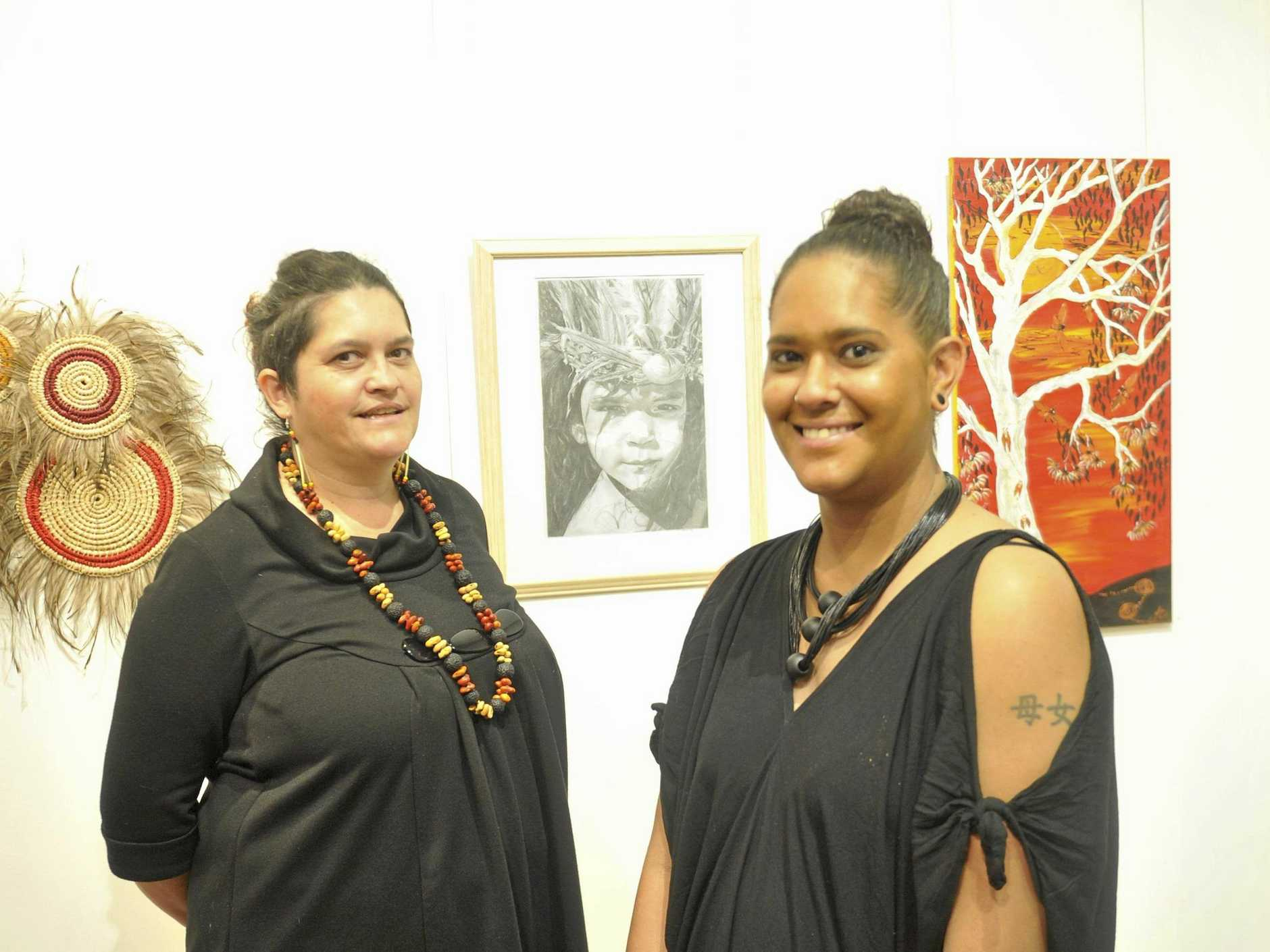 EXQUISITELY EXECUTED: Exhibition judge Bianca Beetson and art prize winner Stacie Fraser with her work  Daughter of a Warrior  in the background.