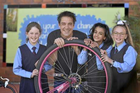 Actor Samuel Johnson with (from left) Adeline Teague, Emily Betros and Amani Holland while bringing his Love Your Sister breast cancer message to Our Lady of Lourdes primary school this morning.