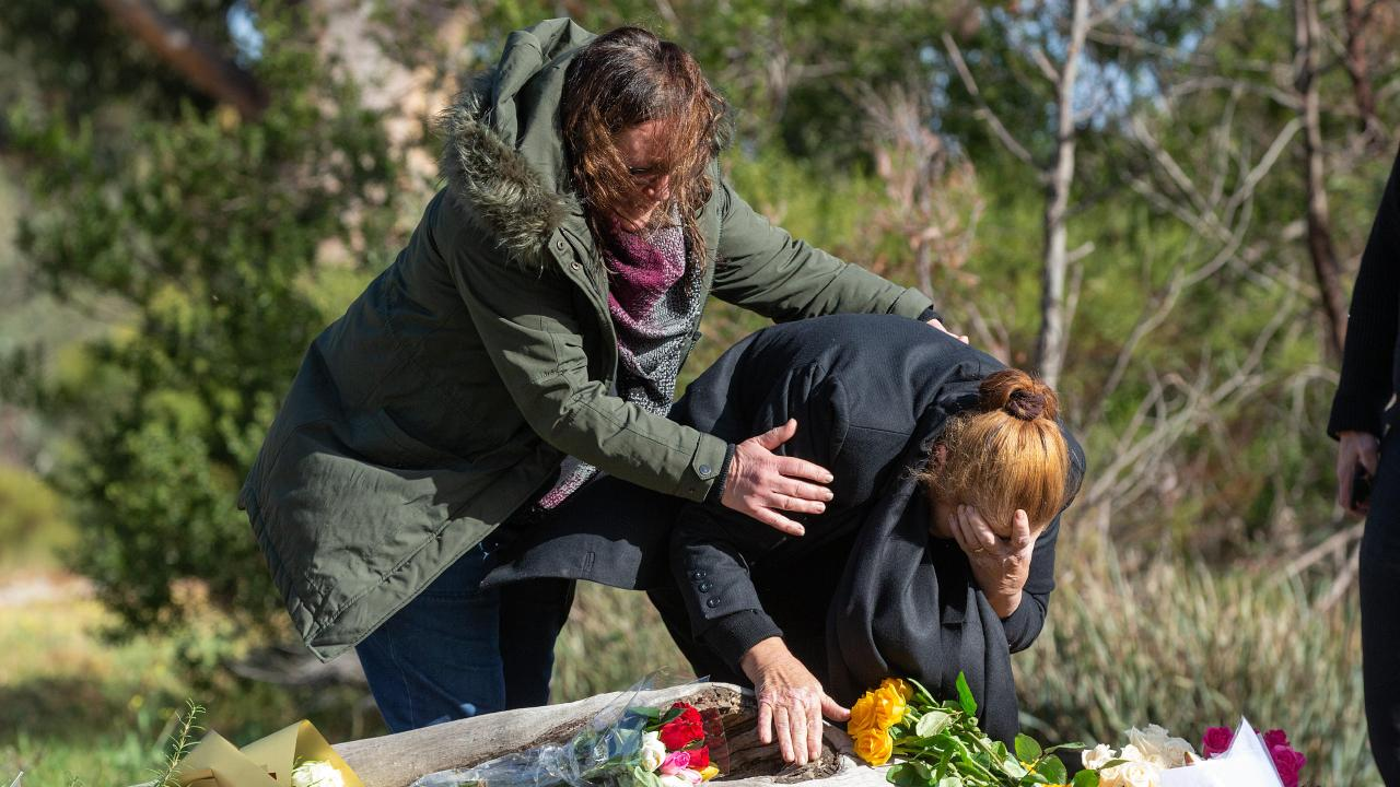 Courntey's mother and grandmother lay flowers at the log where Courtney's body was found. Picture: Sarah Matray