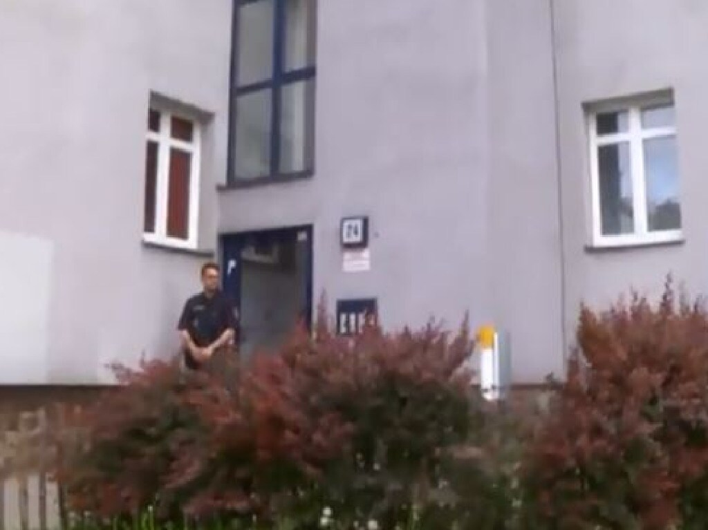 A police officer guards the entrance of the government housing block in Werndlgasse, Vienna, where Vesna, Suzana and Tanja Milosevich starved to death. Picture: Supplied