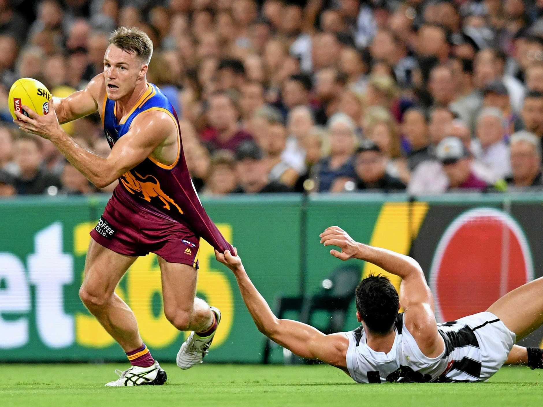 The Lions' Lincoln McCarthy tries to shake the tackle of Collingwood skipper Scott Pendlebury at the Gabba last month. Picture: Darren England/AAP