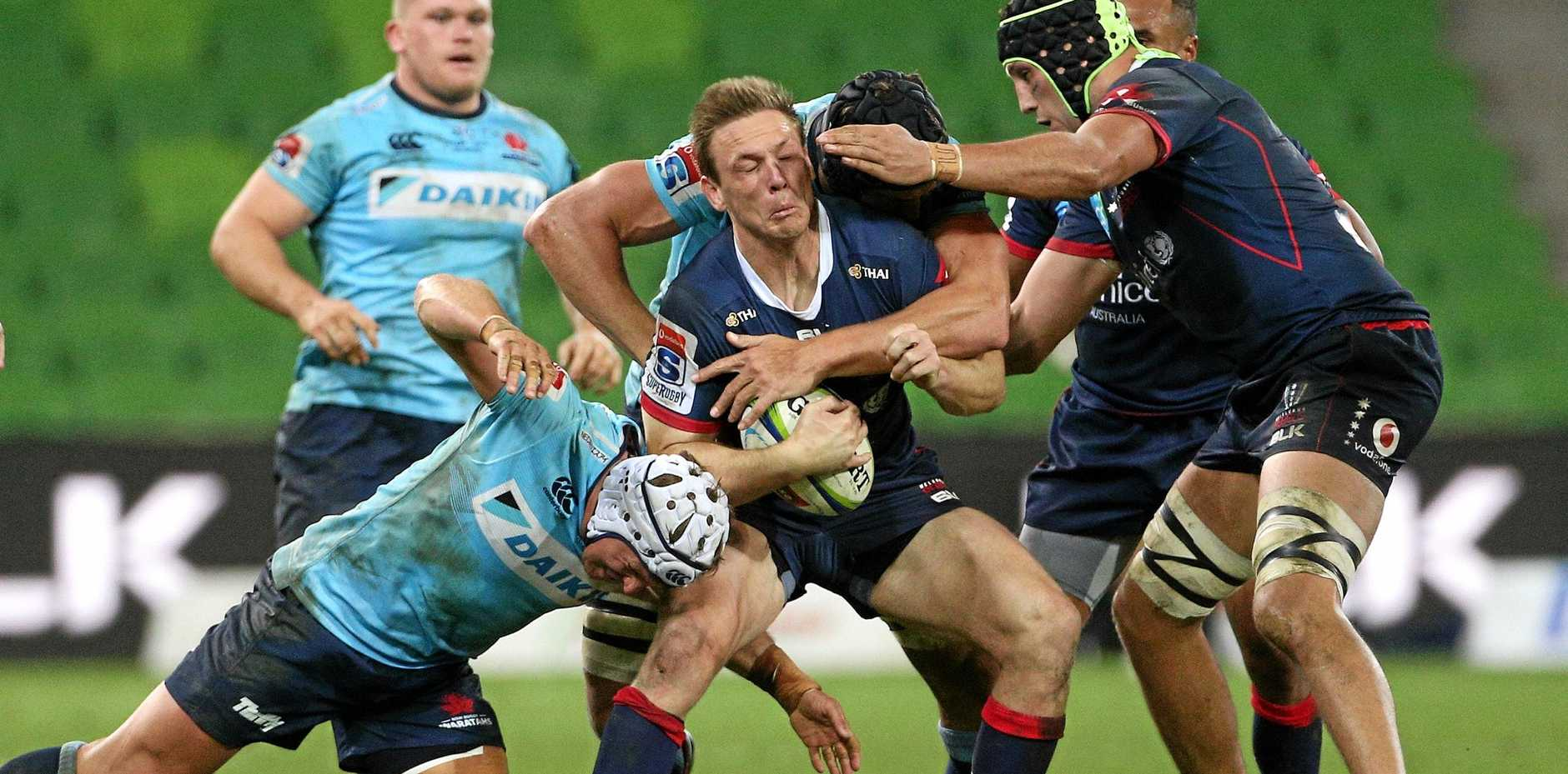 The Rebels' Dane Haylett-Petty feels the force of the Waratahs at AAMI Park on Friday night. Picture: Hamish Blair/AAP