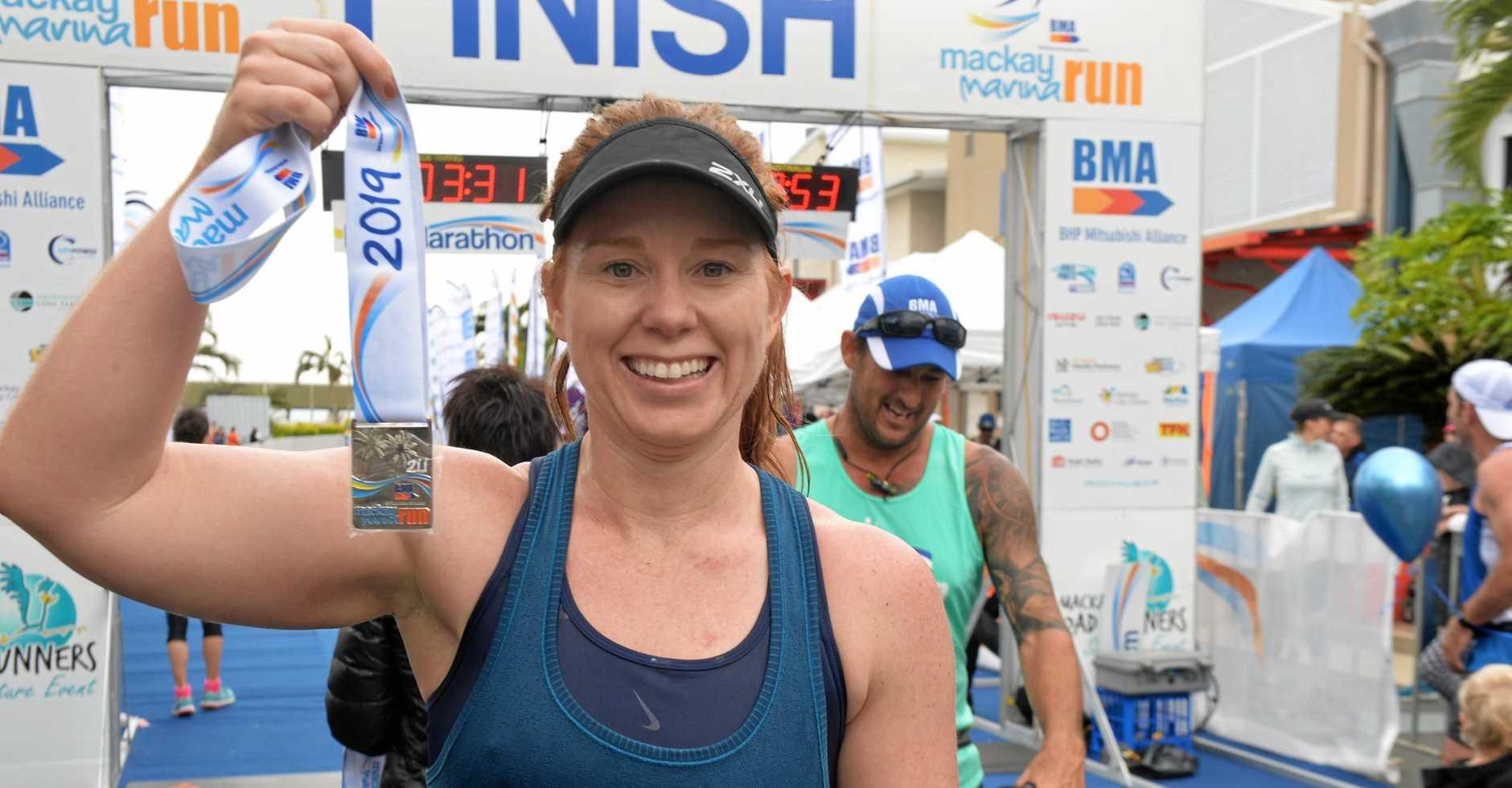 ACHIEVEMENT: Lauren Hay proudly presents her half-marathon medal at the Mackay Marina Run.