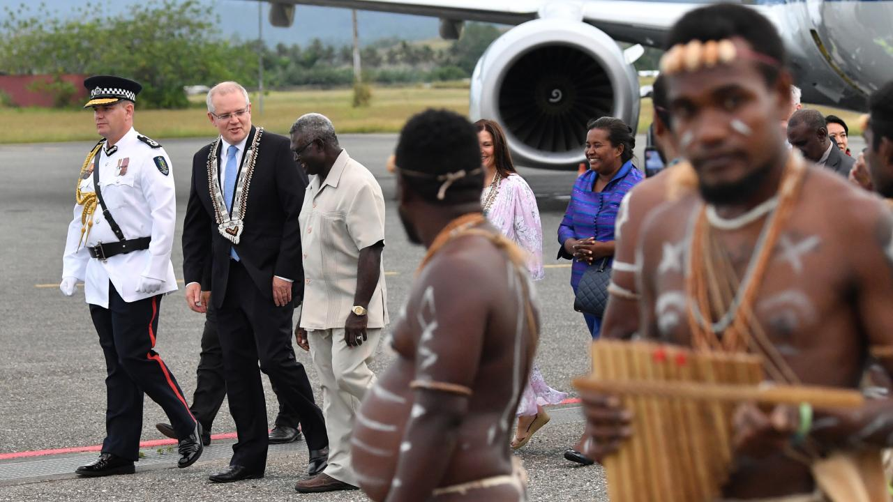 Scott Morrison with Solomon Islands Prime Minister Manasseh Sogavare (centre) after arriving at Honiara International Airport. Picture: AAP