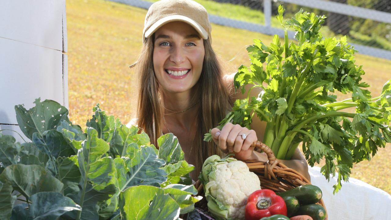 Plant-based advocate Loni Jane with vegetables in her backyard vege patch in the Gold Coast hinterland. Picture Glenn Hampson