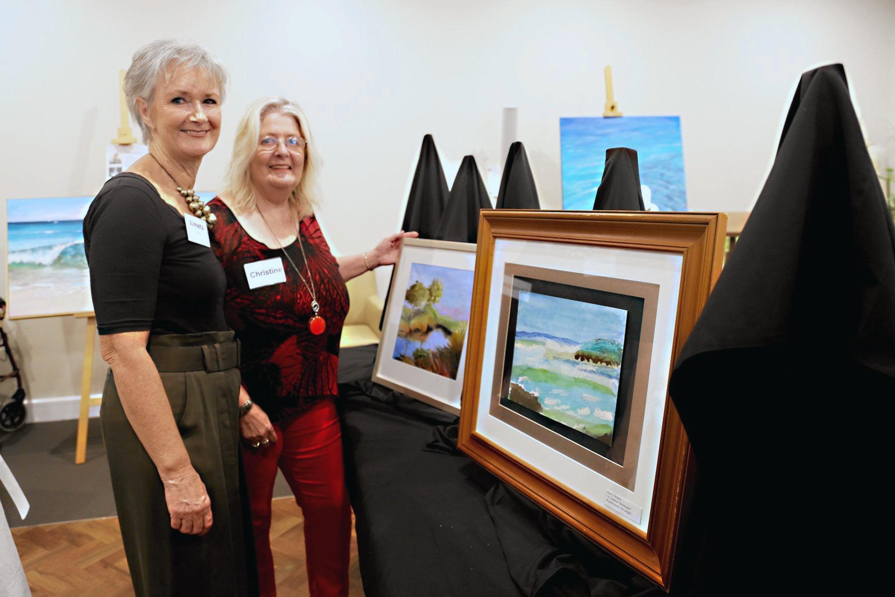 PROUD OF RESIDENTS: Artist and mentor Almeta Lennon (left) and hinterland artist Christine Hopkins peruse the artworks.