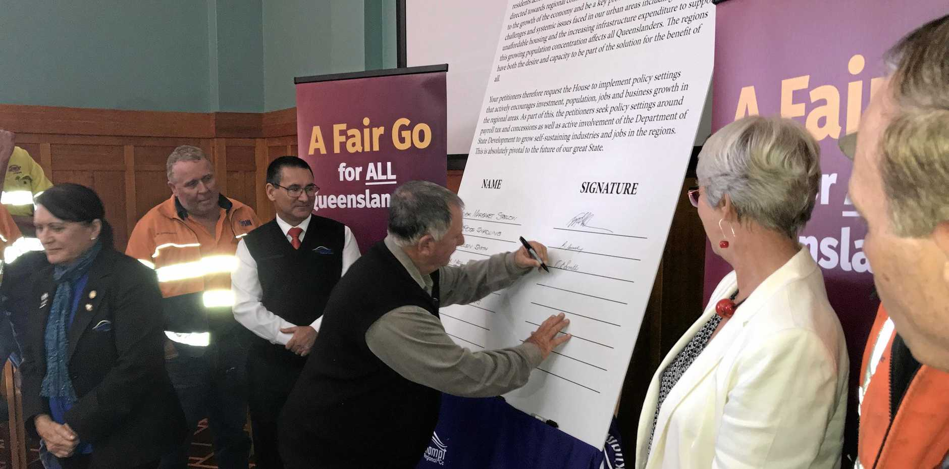 Cr Neil Fisher signing the petition