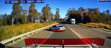 A screen shot from the video shows the police car performing the manoeuvre in front of a truck.
